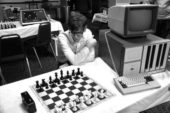 Set over the course of a weekend tournament for chess software programmers thirty-some years ago, the film transports viewers to a nostalgic moment when the contest between technology and the human spirit seemed a little more up for grabs. We get to know the eccentric geniuses possessed of the vision to teach a metal box to defeat man, literally, at his own game, laying the groundwork for artificial intelligence as we know it and will come to know it in the future.